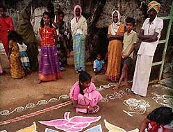 Woman decorate with vibrantly colored rice powder paintings during the Pongal festival